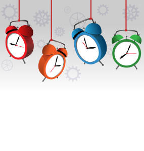 Four multicolored alarm clocks on gray background